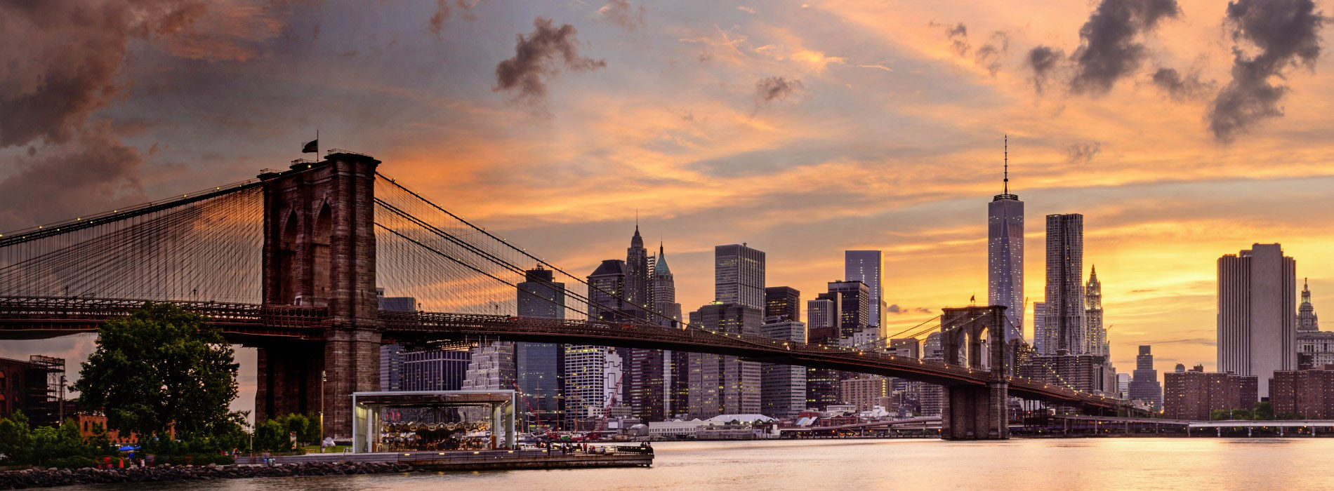 Brooklyn Bridge spanning water and New York skyline at sunset behind.