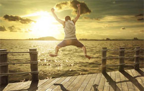 Man in shorts jumping off a short pier with hands hands and legs spread in joy.